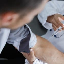doctor injection flu vaccine to patients arm